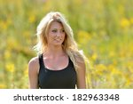 Stunning young blonde archer woman in black tank top standing in a field of goldenrod