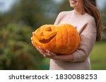 Happy Woman Holds Pumpkin...