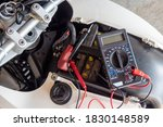 Small photo of a check volt of battery with motorcycle service concept