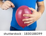Small photo of Conceptual photography. The man holds a red ball near his belly, which symbolizes bloating and flatulence. Then he brings a needle to it to burst the balloon and thus get rid of the problem.