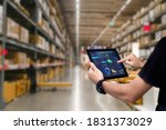 Small photo of Smart warehouse management system.Worker hands holding tablet on blurred warehouse as background