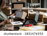 Small photo of Female seller worker online store holding scanner scanning parcel barcode tag packing ecommerce post shipping box checking online retail store orders in dropshipping delivery service warehouse.