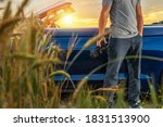 Caucasian Tourist in His 40s with Modern Pro Digital Camera in His Hand and Convertible Vehicle Next to Him. Travel Photography Theme. - stock photo