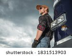 Automotive and Transportation Industry Concept. Caucasian Trucker Driver in His 40s in Front of His Retro Semi Truck Tractor and Cloudy Sky in Background. - stock photo