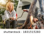 Camping Caucasian Woman in Her 40s Grilling Polish Sausage Directly on Fire in Front of Her RV Recreational Vehicle Camper Van. Campfire Grill Time. - stock photo