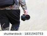 Man holding a camera walking outdoors. Caucasian wildlife photographer with bagpack and a telephoto lens trekking on a yellow grass field. Concept of widlife photography and nature activities.  - stock photo