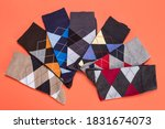 Small photo of seven socks with color patterns of rhombuses lined in a semicircle on orange background, concept