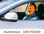 Man inside a car with a pumpkin ...