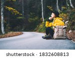 Small photo of Young female hitchhiker by the roadside among autumn forest during fall season. Travel woman hitchhiking. Hiker girl sitting on road with camping backpack. Tourist in yellow raincoat outdoors