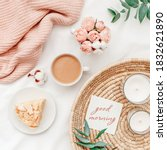Small photo of Wicker tray, cup of coffee, piece of cake, rose flowers, eucalyptus branch, candles, pink knitted plaid or blanket, card with text GOOD MORNING. Breakfast in bed. Stylish home interior decor. Top view