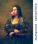 Small photo of Bubble gum. Young woman as Mona Lisa, La Gioconda isolated on dark green background. Retro style, comparison of eras concept. Beautiful female model like classic historical character, old-fashioned.