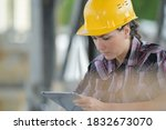 Woman wearing hardhat looking at tablet