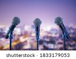 Three microphones over blurred night city background. Art and performance concept. 3D Rendering