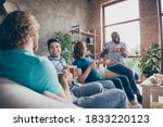 Small photo of Portrait of cheerful four man pals sit divan hold mug beverage beer enjoy talking news in house indoors apartment