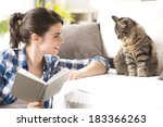 Stock photo smiling woman playing with her cat and holding a book in the living room 183366263