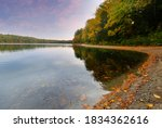 Small photo of Beautiful fall foliage at Walden Pond at sun rise, Concord Massachusetts USA. Walden Pond is a lake in Concord, formed by retreating glaciers 10,000–12,000 years ago.