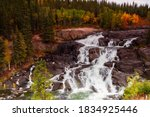 Early fall colours provide contrast to the stark rock framing Cameron falls along the Ingraham Trail in Canada