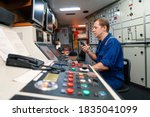Small photo of Marine engineer officer controlling vessel engines and propulsion in engine control room ECR. Ship maintenance Start or stop of main engine