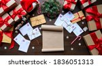 Small photo of Merry Christmas decorated wooden table with wish list, post mail letters envelopes, gifts boxes, presents with red ribbons. Xmas Santa desk workplace background concept. Top view above, flat lay.