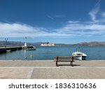 Virw of port of the city of Nafplion in Greece during Autumn. Lighthouse and castle. Bench and fishing boat. Blue sky with broken clouds