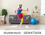 Happy goofy young man in retro sportswear decided to start fitness training and now is exercising with dumbbells and laughing, motivating you to do sports, keep fit and lead healthy lifestyle too
