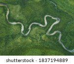aerial nature landscape of winding river in green field, top view of beautiful texture from drone above
