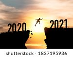 Small photo of Welcome merry Christmas and happy new year in 2021,Silhouette Man jumping from 2020 cliff to 2021 cliff with cloud sky and sunlight.