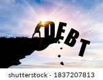 Small photo of Eliminate or get rid of debt concept , Silhouette man pushed off debt wording a cliff with blue cloud sky and sunlight.
