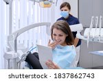 Small photo of Happy middle aged woman with doctor dentist looking in mirror at teeth, sitting in dental chair. Medicine, dentistry and health care concept