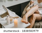 Small photo of Dry brushing body brush for exfoliating dry skin, lymphatic drainage and cellulite treatment. Woman brushing skin leg with dry wooden brush to prevent cellulite and body problem in bedroom at home