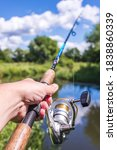 Small photo of Male hand holding a fishing rod/Male hand holding a fishing rod from the first person. On a sunny day