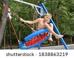 Small photo of Boy swinging on a swing on beach in summer. child on a large wicker swing is having fun. summer vacation vacations children outdoor