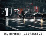 Small photo of Biker going through raining road with traffic lights at night. Out of focus city life on a rainy day. Drops of rain stopped in motion against lights. Rain in city road, traffic main roads traffic jams