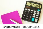 Small photo of The word Upsurge , on a calculator, next to a notepad with a pen on a white background