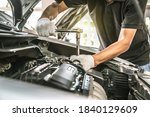 Close-up hands of auto mechanic are using the wrench to repair a car engine in auto car garage. Concepts of car care fixed repair and services. - stock photo