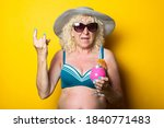 Old woman in swimsuit with cocktail shows goat gesture, rock goat on yellow background. - stock photo