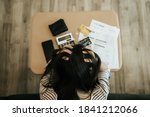 Small photo of Top view of stressed woman trying money to pay credit card debt and many expenses bills such as electricity bill,water bill,internet bill,phone bill during covid-19 or coronavirus outbreak at home