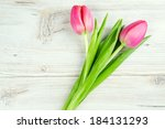 Two Pink Tulips On White Woode...