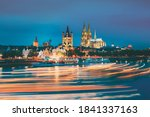 Cologne, Germany. Great St. Martin Church And Dom In Cologne At Evening With Reflection In River Rhine. Evening Blue Hour. Light Trails On Water From Pleasure Boats In Long Exposure Photography