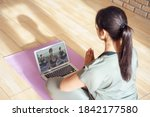 Small photo of Young woman meditating watching live online tv pilates group class tutorial on laptop computer at home doing yoga virtual training fitness workout meditation exercise stream. Over shoulder screen view
