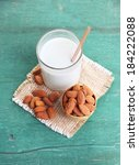 Small photo of Almond milk in glass with almonds in bowl, on color wooden background