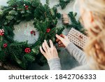Woman makes a fir wreath for...