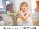 Child Cuddles With Her Soft...