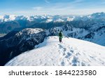 Small photo of Tourist with a backpack and mountain panorama. Climber in a green jacket climbs a mountain against a blue sky. Hiker with backpack standing on top of a mountain and enjoying view. Adventure concept