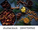 Small photo of Ingredients for Christmas fruit cake (nuts and dried fruits). Ceramic bowl with nuts and soft fruit soaked in brandy. Top view.