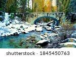 Small photo of Winter forest river bridge snow. Arched stone bridge in winter forest. Forest river bridge. River bridge in snowy forest
