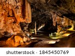 Small photo of In mountain cave scene view. Cave in lights. Cave in mountains. Mountain cave view