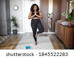 Small photo of young african black woman keep balance, stand on one leg, yoga time at home. concentrated on yoga, meditation