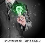 business man touching light of... | Shutterstock . vector #184555310