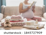 Small photo of Pregnant woman is getting ready for the maternity hospital, packing baby stuff. pregnant woman preparing and planning baby clothes. List of things in the hospital.